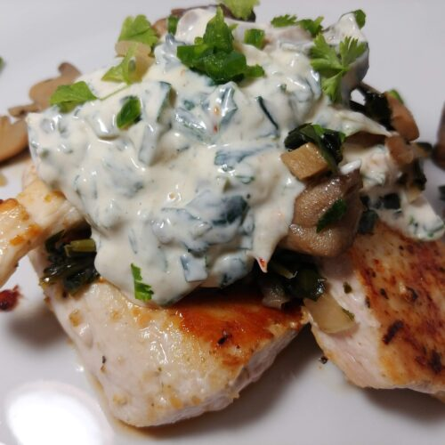 pan searched chicken topped with spinach dip and mushrooms