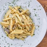 pasta with cream sauce and mushrooms in white dish and parsley