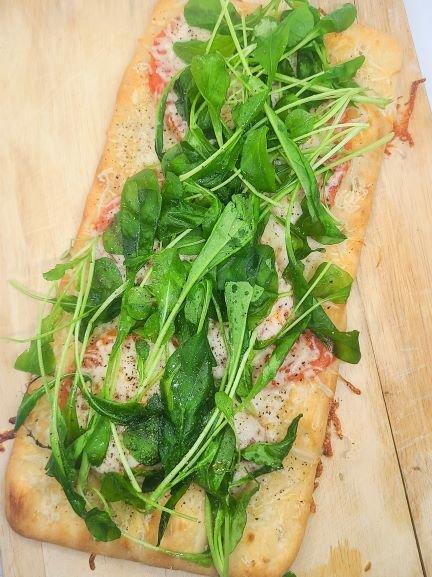 fresh arugula on top of a flatbread pizza