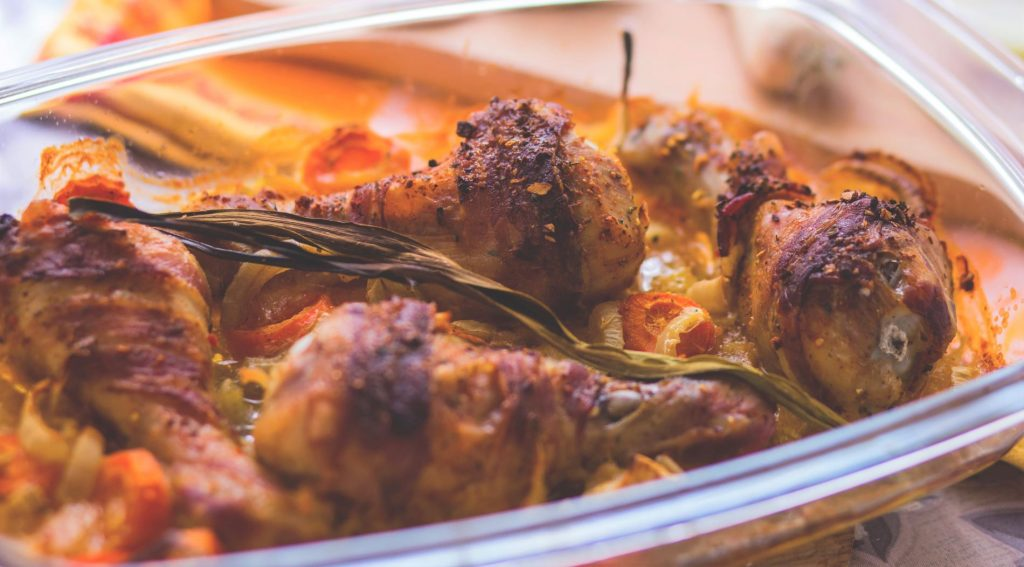 Bacon Wrapped Chicken Drumsticks baked in the oven in a glass dish