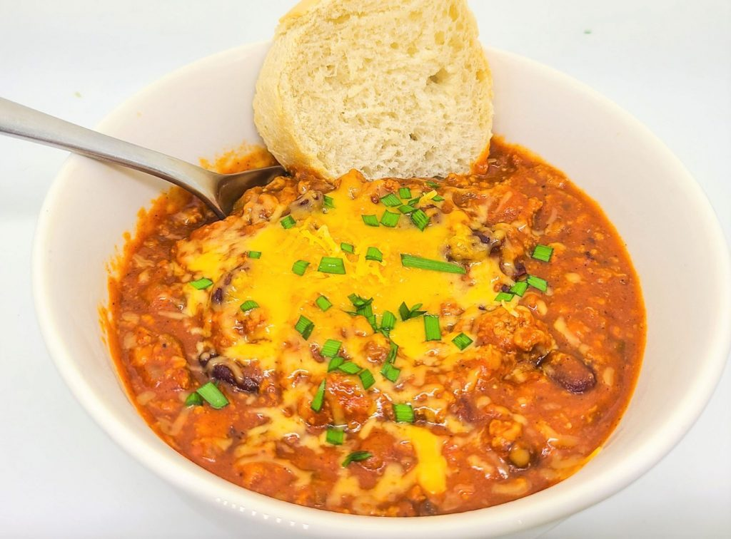 delicious ground turkey chili recipe with red beans in a white bowl topped with cheddar cheese